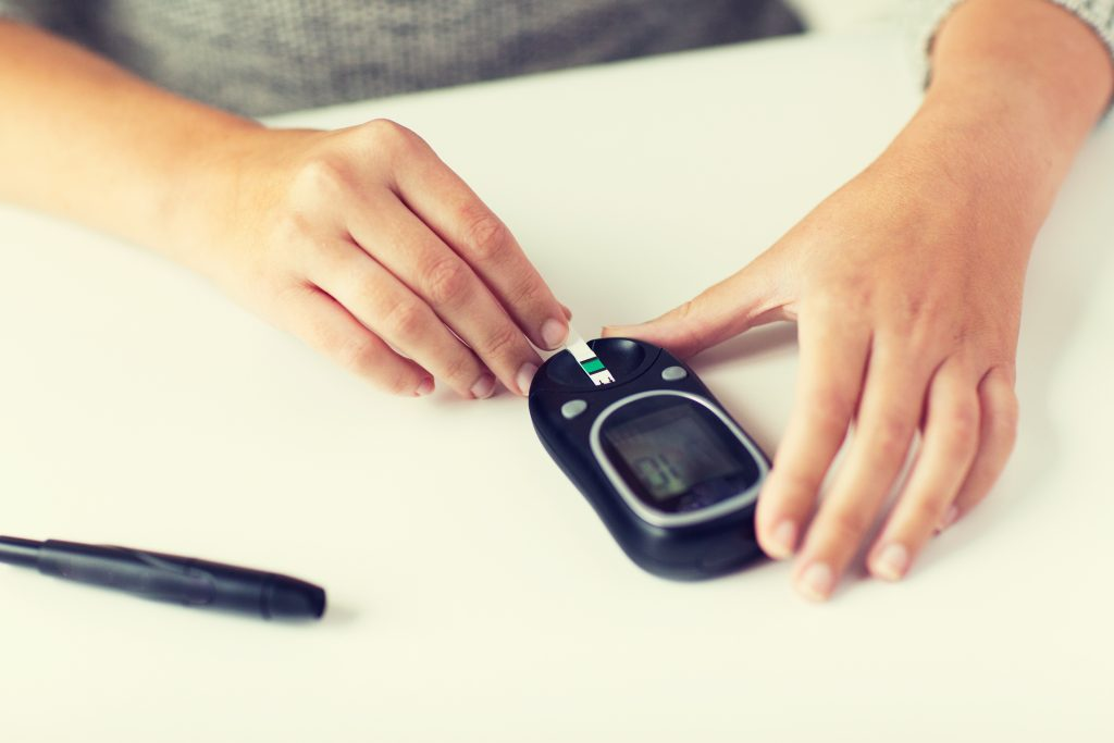 woman managing her diabetes through a blood test by glucometer